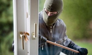 Masked man using crow bar to open window