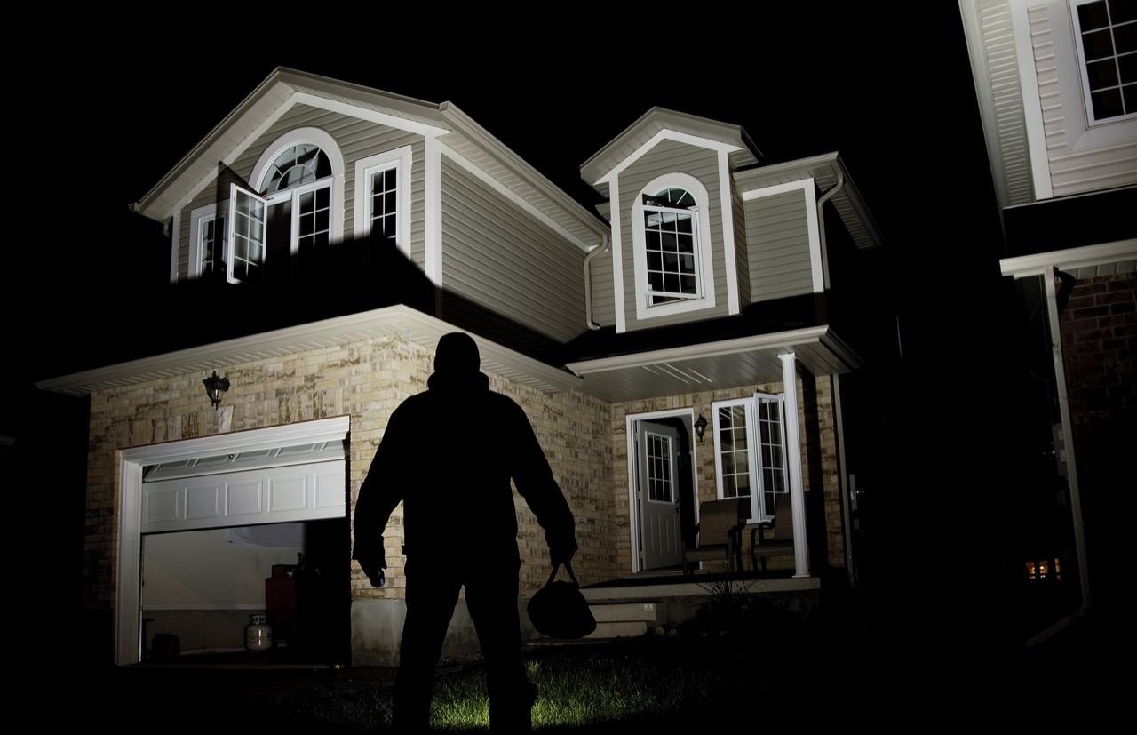 Man in shadow standing in front of house
