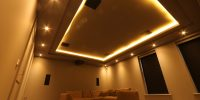 Cinema room with concealed ceiling lighting and beige sofa